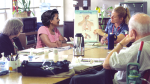 Two woman and a man sitting at table listening to healthcare provider give presentation with illustration of respiratory system.