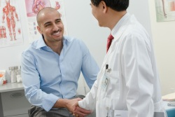 Man shaking hands with male physician in an exam room