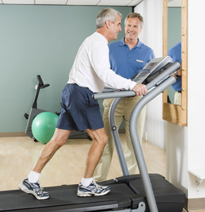 Man on treadmill with healthcare provider standing next to treadmill, supervising man's exercise.