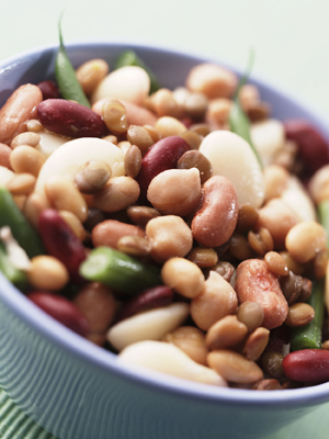 Close-up of many varieties of cooked beans in a bowl.