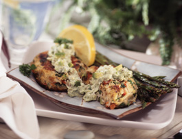 Crab cakes on a plate with lemon and asparagus.
