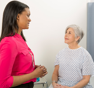 Older woman in hospital gown talking with her doctor