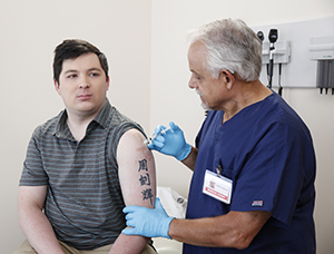 Healthcare provider giving man injection in upper arm.