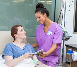 Healthcare provider caring for woman having infusion treatment.