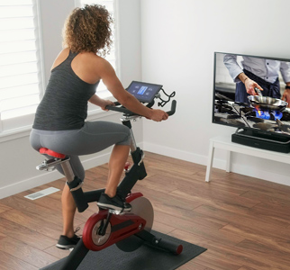 Woman watching TV and pedaling on an exercise bike