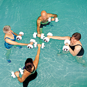 Four people with hand weights in shallow part of swimming pool.