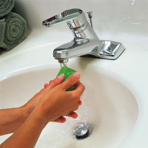 Hands holding a bar of soap under running water in a sink
