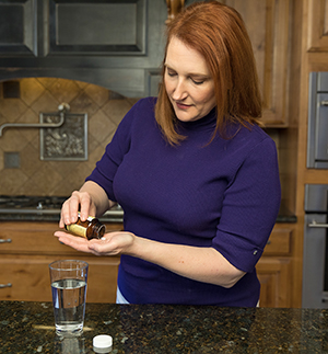 Woman taking pills in kitchen.