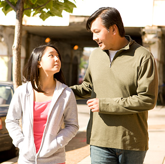 A father and his teenaged daughter walking down a street having a conversation.