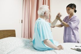 Therapist manipulating the arm of an older man who is in the hospital