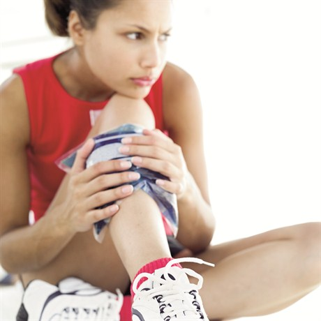 Photo of young woman holding an ice pack to her shin