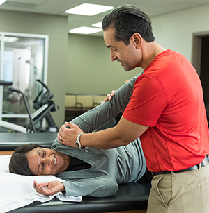 Physical therapist working with woman on arm stretches.