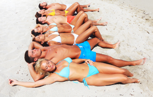 Group of young people lying on the beach and sunbathing.