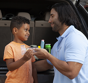 Man handing boy a metered-dose inhaler with spacer and mask.