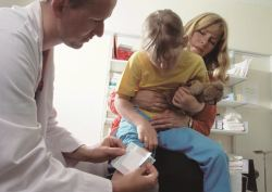 Doctor placing bandage on child's leg