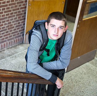 Teenaged boy in the stairwell of a high school looking up to the camera.