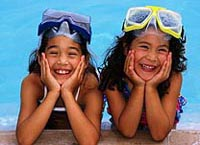 Picture of two young girls giggling by the side of the pool