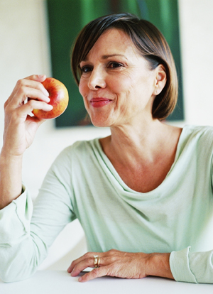 Mature woman eating an apple.
