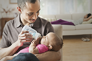Man feeding baby with bottle.