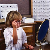 Picture of a young girl trying on a pair of eyeglasses