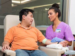 Healthcare provider caring for man donating blood.