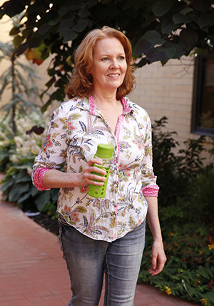 Woman holding water bottle, walking outdoors