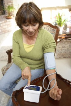 Middle aged woman taking her blood pressure with a home monitor.