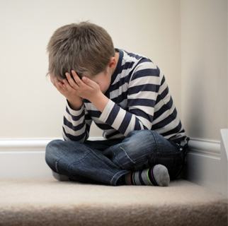 Child in a corner with his hands over his face as if afraid.