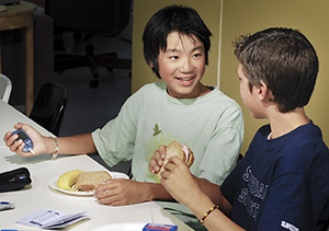 Boy at school using a glucometer during lunch.
